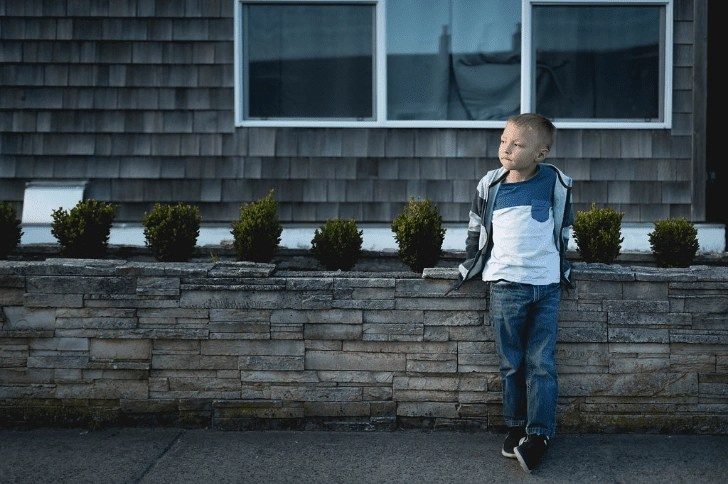 Cute boy standing in front of a Cape Cod style home | Global Munchkins photo by Kelsey Smith Photography