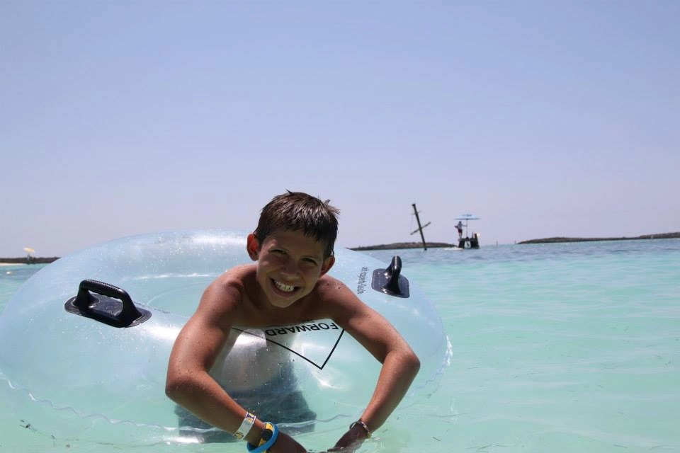 boy in tube in water at Castaway Cay Disney Cruise Line's Private Island | Global Munchkins