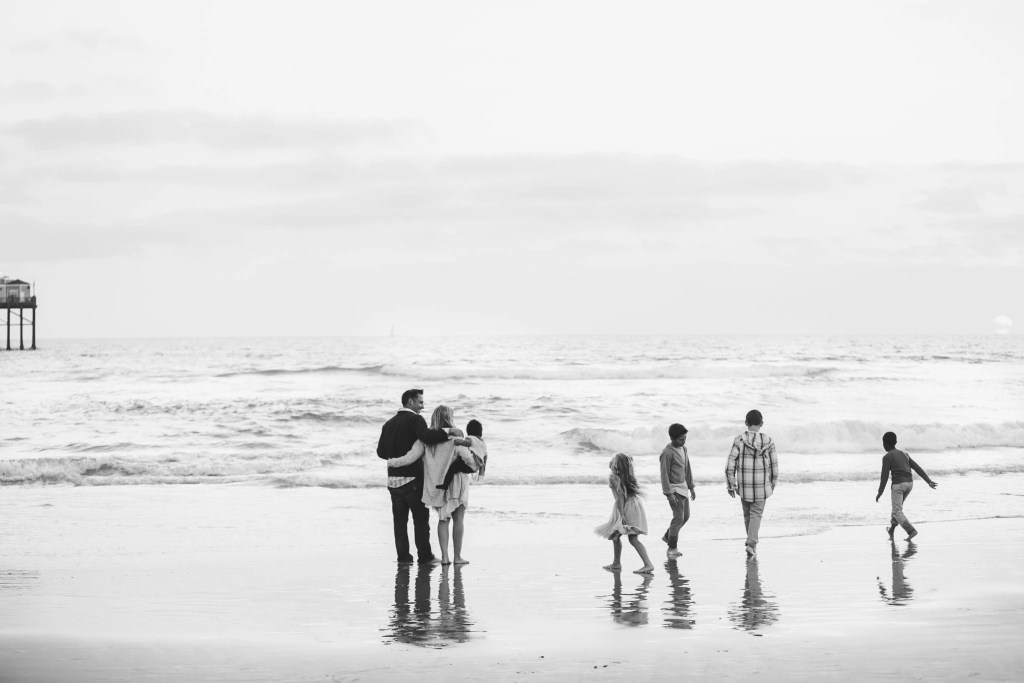 Family staring at the ocean watching their kids play | Global Munchkins