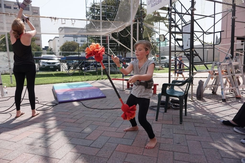 Playing with Devil Sticks at SwingIt Trapeze in Anaheim while waiting for her turn to swing | Global Munchkins