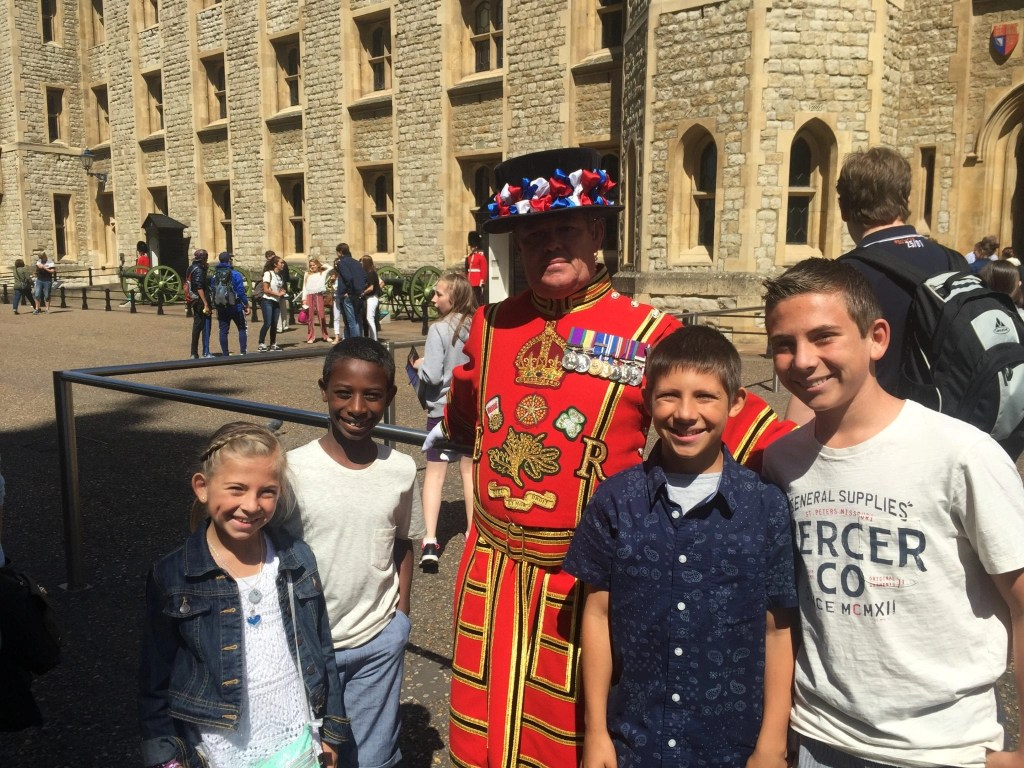 Kids taking a picture with the guards at the Tower of London. Guards in their special uniforms | London with Kids | Global Munchkins
