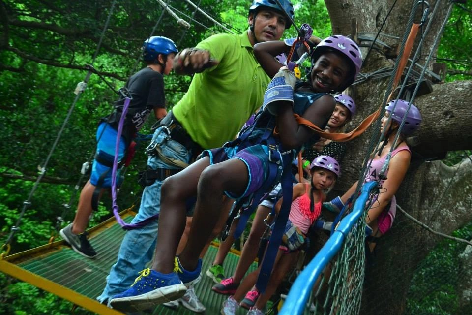 Black boy on zipline in Costa Rica with instructor giving him a push | Global Munchkins