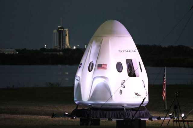 A full-size model of the Crew-1 spacecraft module sits near the launch pad as a SpaceX Falcon 9 rocket is seen at launch complex 39A in the distance at the Kennedy Space Center in Florida on Nov. 15, 2020.