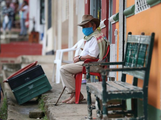 Wearing a mask to curb the spread of the new coronavirus, a man sits on his front porch in Campohermoso, Colombia, Thursday, March 18, 2021. According to the Health Ministry, Campohermoso is one of two municipalities in Colombia that has not had a single case of COVID-19 since the pandemic started one year ago.