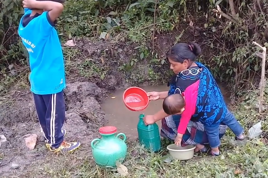 A woman collects water in Las Joyas, Guatemala.