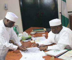 Governor Aminu Waziri Tambuwal, with the Clerk of the Sokoto State House of Assembly, Muhammad Mainassara Ahmad, during the signing of the Primary Healthcare Development Agency Amendment bill (2015) in Government House, Sokoto