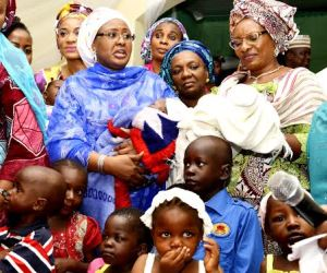Wife of President Muhammadu Buhari (middle) carrying a baby during her visit to an orphanage home in Gwako Gwagwalada, Abuja, FCT, on Thursday, 24/9/15