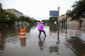 Mary Baldrick of Isle of Palms, South Carolina, wades through flooded Front Street in Georgetown, South Carolina October 4, 2015. REUTERS/Randall Hill