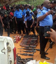 Edo State Commissioner of Police, Mr. Chris Ezike, addressing newsmen on arms and ammunition as well as money recovered from fleeing armed robbers who attacked two commercial banks in Igarra, in Igarra, Akoko-Edo Local Government Area of Edo State, Tuesday.