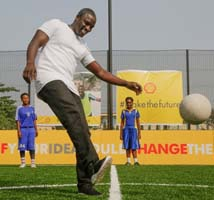 Akon kicks the ball on the new Shell kinetic pitch with students in Lagos