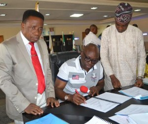 Ekiti State Governor, Mr Ayodele Fayose ( middle) signing the ‎ 2016 appropriation bill into law while the Speaker, Ekiti State House of Assembly, Pastor Kola Oluwawole ( left) and the Deputy Speaker, Hon Segun Adewumi ( right) watch during a brief ceremony held at the main chamber of the Governor's Office, Ado Ekiti on Tuesday.
