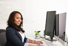 woman wearing black cardigan sitting on black mesh back rolling armchair and using silver imac
