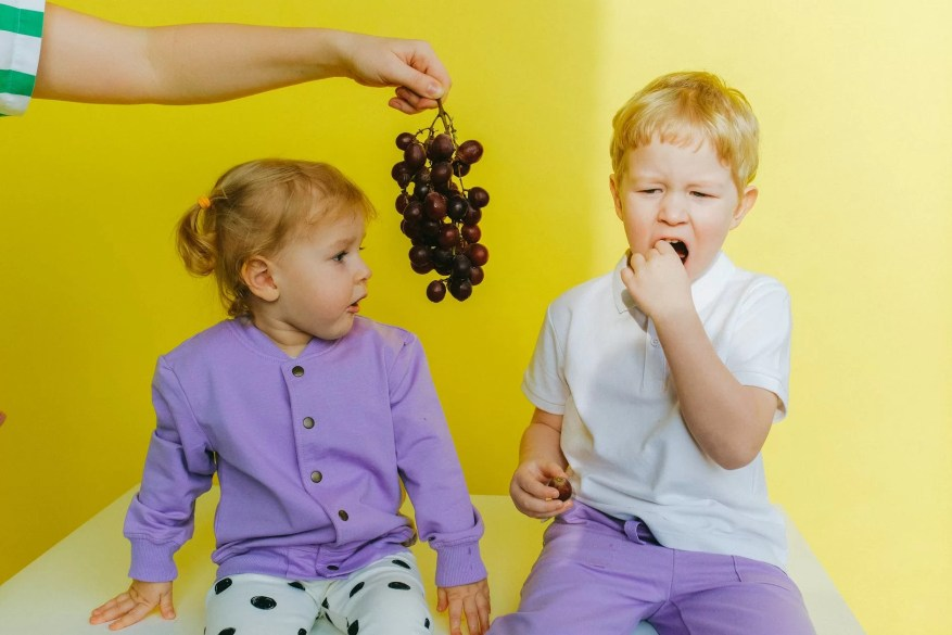 person holding grapes between boy and girl