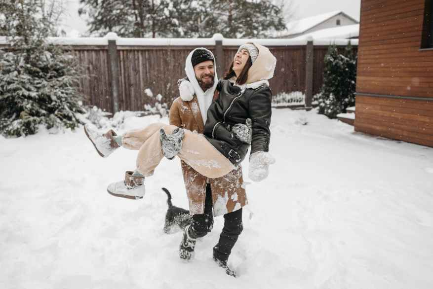 man and woman playing on snow covered backyard