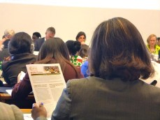 """Audience members at ILC reading WIEGO's position paper, """"Waste Pickers: The Right to be Recognized as Workers."""" Photo: Lucia Fernandez."""