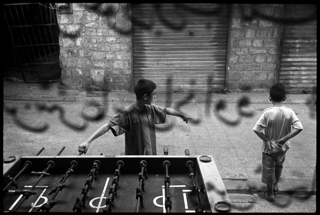 TYRE, LEBANON - August 8, 2006: Two young boys seen through a coffee shop window in Tyre, Lebanon, August 8, 2006. (Photo by Farah Nosh/Getty Images)