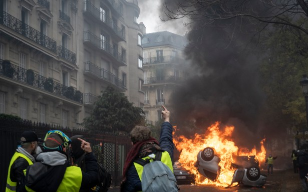 """PARIS, FRANCE - DECEMBER 01: Cars are put on fire nearby the Arc de Triomphe, on December 1, 2018 in Paris, France. The demonstrators, known as """"gilets jaunes"""" or """"yellow vests,"""" have protested across France for the last two weeks, demanding a reduction in fuel prices. French law requires drivers to carry yellow vests in case of accident. (Photo by Veronique de Viguerie/Getty Images)"""
