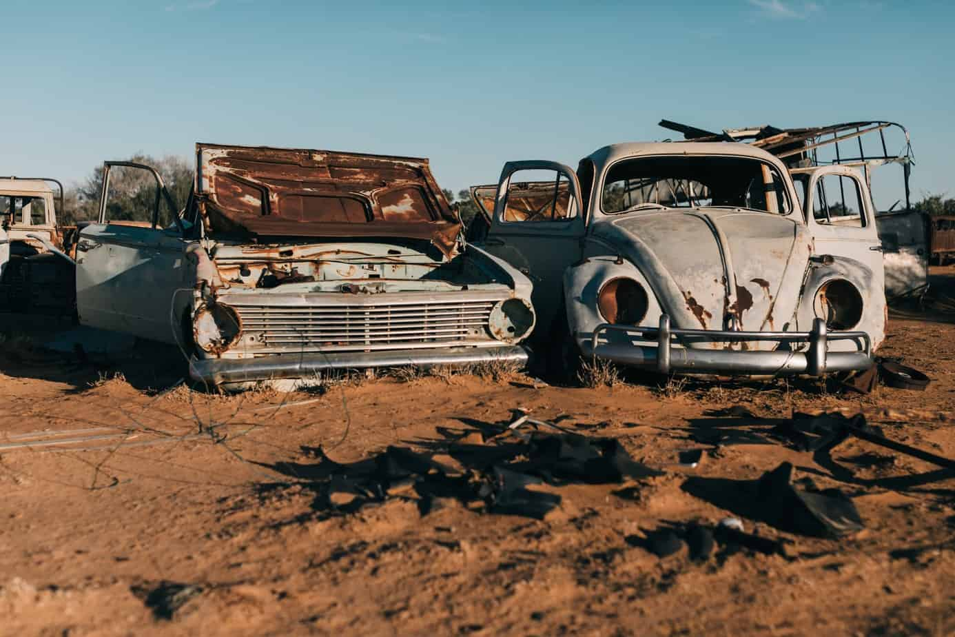 damaged retro cars in desert under blue sky