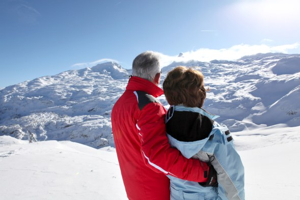 Middle-aged couple stood on secluded snowy mountain