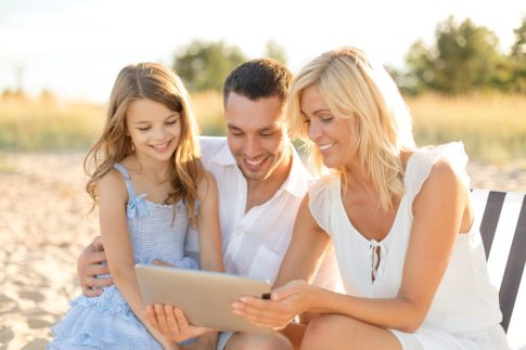 smiling family at beach with tablet pc computer