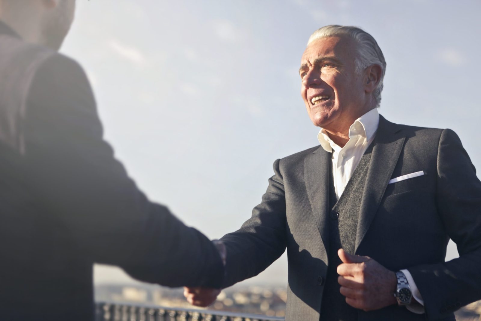 a man in black suite shaking hand