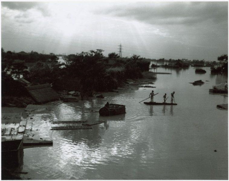 Japanese refugees paddle on makeshift raft through flooded village