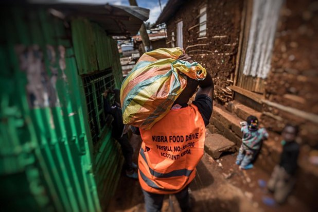 """Un homme en gilet de sécurité portant l'inscription """"Kibra Food Drive"""" porte un gros sac de jute sur son épaule pendant une distribution de nourriture dans le plus grand quartier informel de Nairobi."""