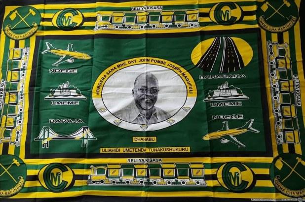 Un pagne vert et jaune, les couleurs du CCM, représente John Magufuli au centre, entouré des symboles de ses réformes.