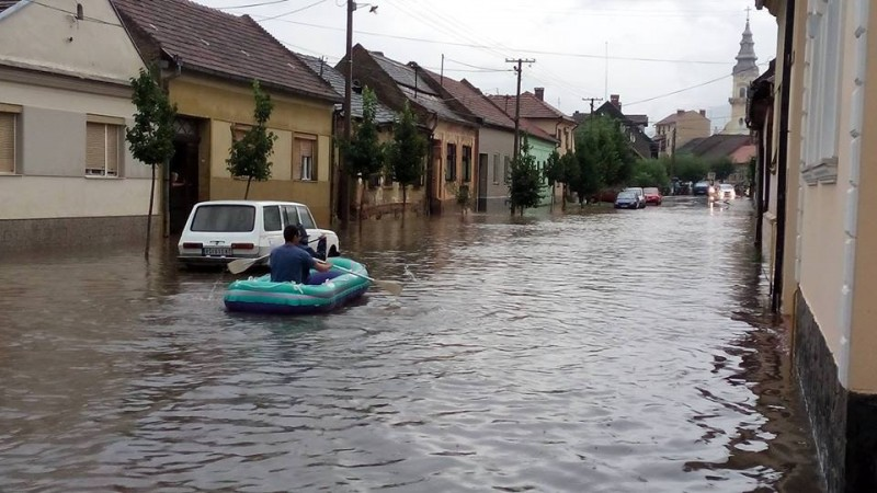 A man uses a boat to navigate the streets in Vršac, Serbia during a new wave of flooding in July 2014. Photos collected by Nenad Kiss from social media users, widely circulated online.
