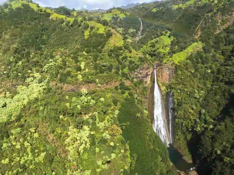 Waterfall in Kauai from a helicopter by Nikki from She Saves She Travels