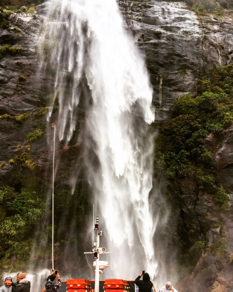 Boating under a waterfall, Milford Sound, Fiordland National Park, New Zealand