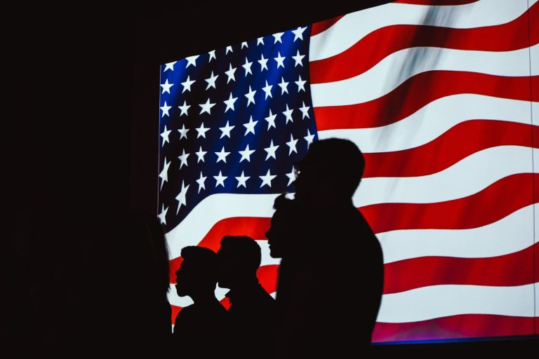 silhouette of four person with flag of united states background