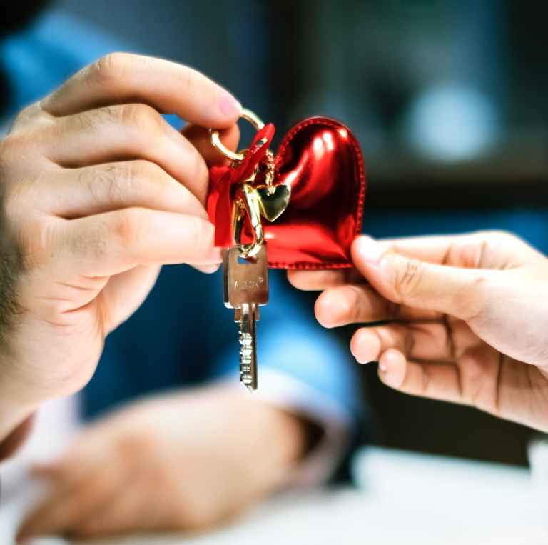 selective focus photography of two person s hands holding gray key with red heart keychain