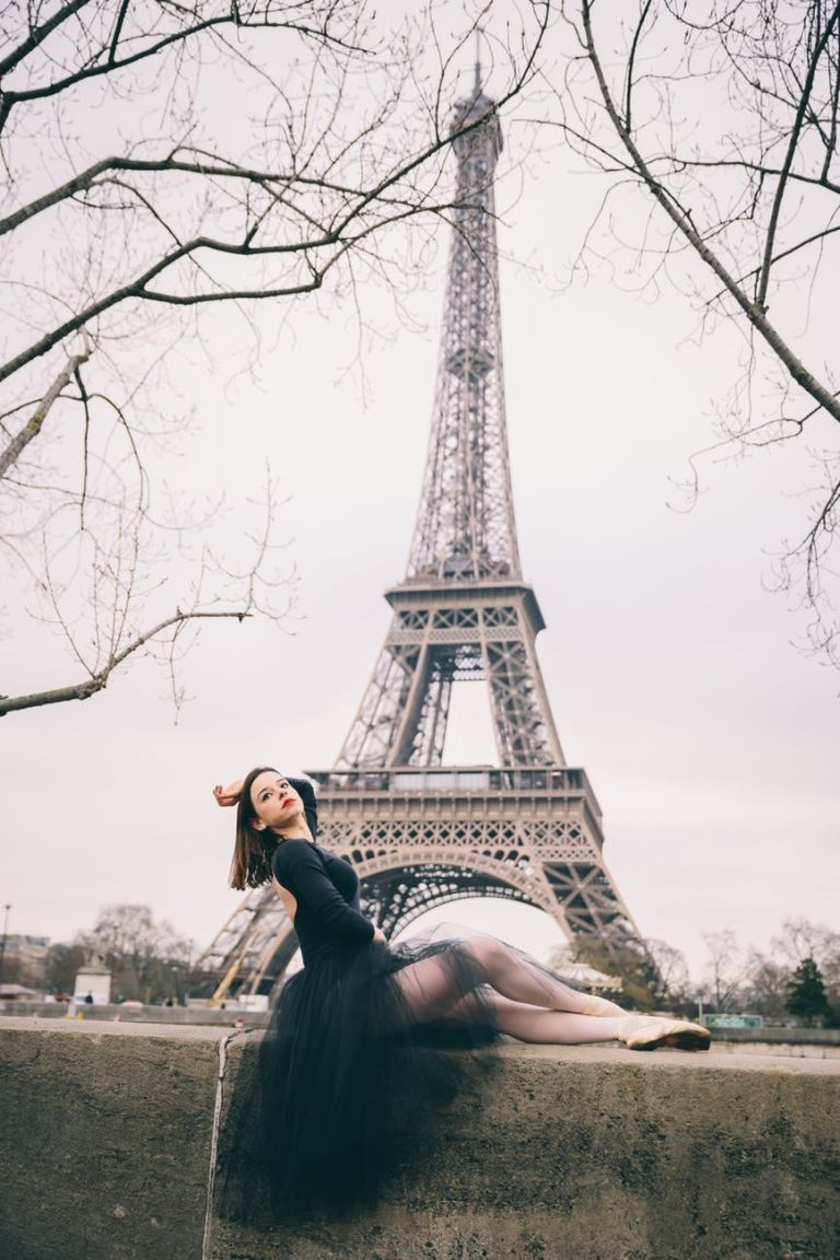 photo of posing ballerina on concrete block with the eiffel tower in the background