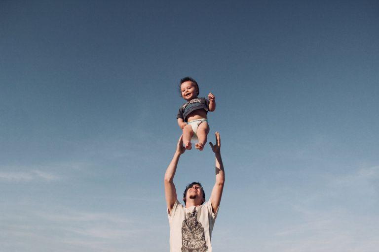 photo of man in raising baby under blue sky