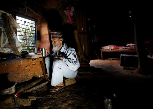 """Durga Kami, 68, who is studying in the tenth grade at Shree Kala Bhairab Higher Secondary School, drinks tea as he prepares dinner at his one-room house in Syangja, Nepal, June 4, 2016.  REUTERS/Navesh Chitrakar. SEARCH """"DURGA KAMI"""" FOR THIS STORY. SEARCH """"THE WIDER IMAGE"""" FOR ALL STORIES"""