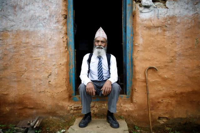 """Durga Kami, 68, who is studying tenth grade at Shree Kala Bhairab Higher Secondary School, poses for a picture wearing his school uniform at the door of his one-room house in Syangja, Nepal, June 5, 2016.  REUTERS/Navesh Chitrakar. SEARCH """"DURGA KAMI"""" FOR THIS STORY. SEARCH """"THE WIDER IMAGE"""" FOR ALL STORIES.    TPX IMAGES OF THE DAY"""