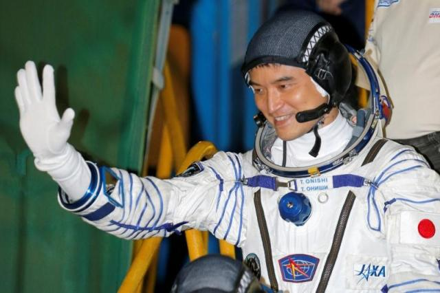 The International Space Station (ISS) crew member Takuya Onishi of Japan gestures close to the rocket prior the launch at the Baikonur cosmodrome, Kazakhstan, July 7, 2016. REUTERS/Dmitri Lovertsky/POOL