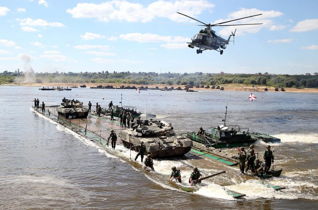 Russian soldiers take part in the Open Water competition for pontoon bridges, part of the International Army Games 2016 in the town of Murom, Russia.