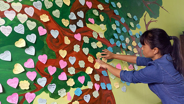 A teacher at Yingjiang No 3 High School posts students' love messages in the school's Youth Love Station on June 22. YANG WANLI/CHINA DAILY