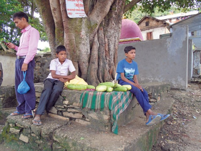 Two boys sell cucumbers near the Krishna Mandir in Mangalsen, Achham. (Damara)