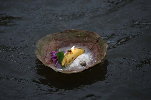 An offering offered by a devotee (not pictured) in memory of his deceased father floats on the Bagmati River during Kuse Aunse (Father's Day) at Gokarna Temple in Kathmandu, on September 1, 2016. Photo: Reuters