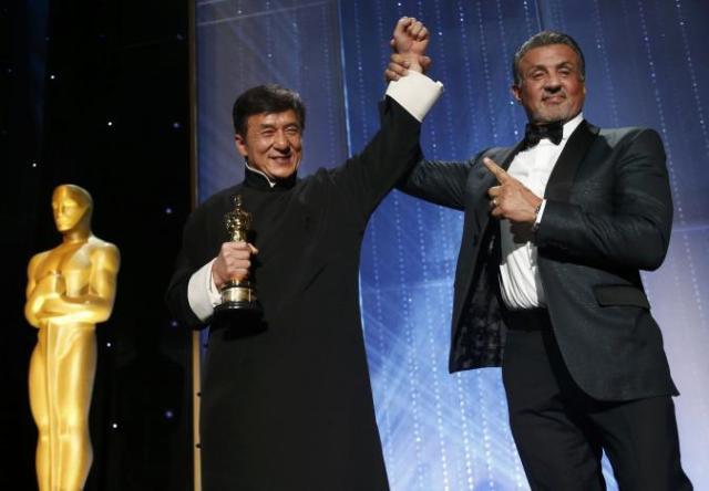 Actor Jackie Chan is congratulated by fellow actor Sylvester Stallone (R) after accepting his Honorary Award at the 8th Annual Governors Awards in Los Angeles, California, U.S.