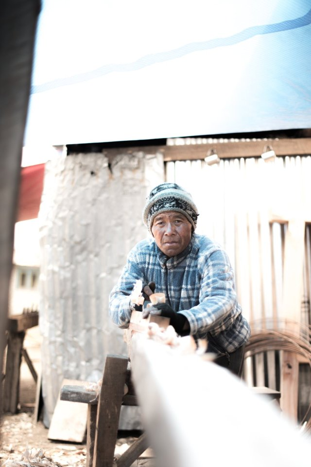 Lobsang, a carpenter who has travelled from Okhaldhunga, planes a wooden beam. He is one of many volunteers from other regions who have come to Langtang to help in reconstruction