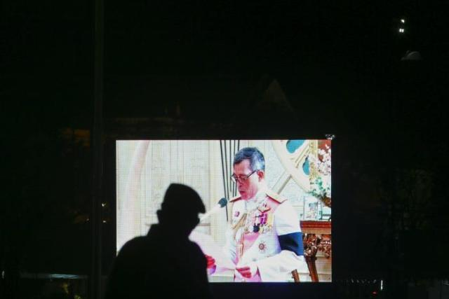 A military officer watches a television screen showing Thailand's new King Maha Vajiralongkorn Bodindradebayavarangkun speaking after he accepted an invitation from parliament to succeed his father, King Bhumibol Adulyadej, who died in October, at the Dusit Palace in Bangkok, Thailand, December 1, 2016. REUTERS/Athit Perawongmetha