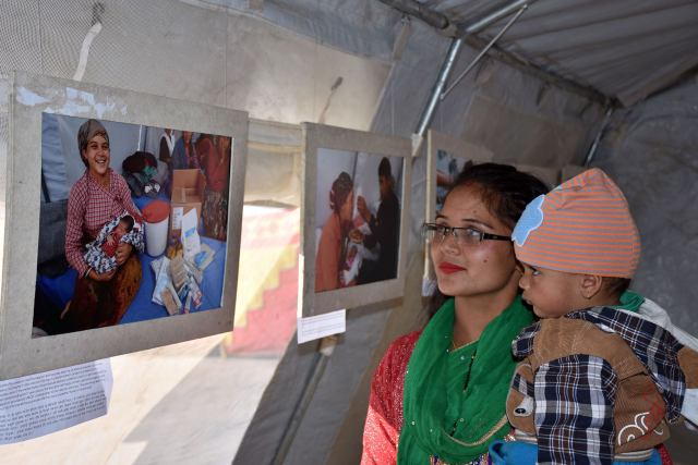 Sushila Phuyal and her 15-month-old son look at their photo displayed at UNICEF's 'Under the Tent' photo exhibition