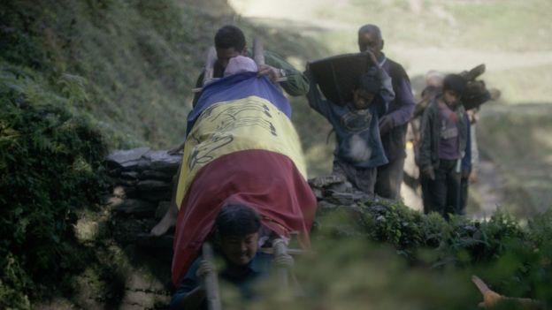 Chandra and Suraj carry the body of their father, draped in a royalist flag