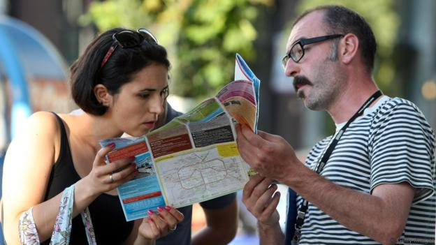Tourists look at a map of Berlin on August 15, 2012 in Berlin, Germany. In 2010, nine million tourists visited the German capital, and ten million came in 2011, a new record. Tourism, a major industry for the city since the fall of the Berlin Wall, contributes 9 billion euros (USD 11.1 billion) into the local economy annually, and has a high employment impact, with 230,000 Berliners earning a living in the tourism sector. The increase in visitors is not limited to Berlin; 75 out of 80 German cities reported more tourists in 2011 over the previous year.  (Photo by Adam Berry/Getty Images)