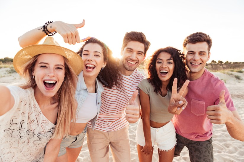 Group of happy young friends in summer clothes taking a selfie while standing at the beach