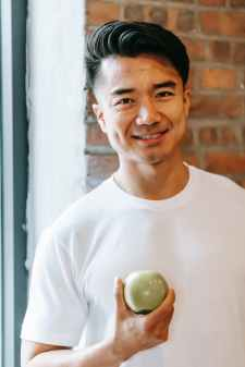 content asian man with green apple